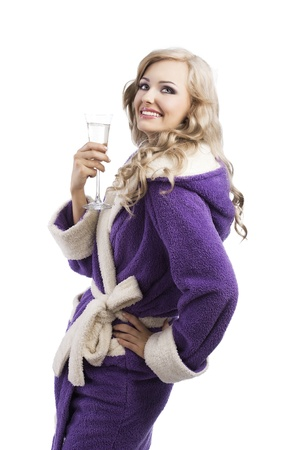 blond pretty expressive blond girl in purple bathrobe drinking from a glass of white wine happy, she looks up, laughs and has her left hand on left hip, takes the glass with right hand photo