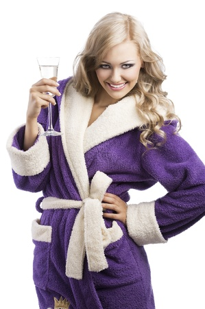 blond pretty expressive blond girl in purple bathrobe drinking from a glass of white wine happy, she is in front of the camera, laughs and takes the glass with right hand and has the left hand on her hip photo