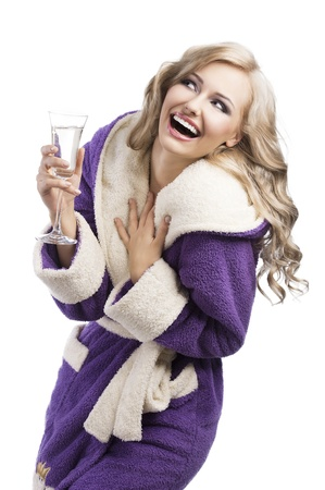 blond pretty expressive blond girl in purple bathrobe drinking from a glass of white wine happy, she laughs, looks up, and takes the glass with right hand and has the left hand on her chest photo