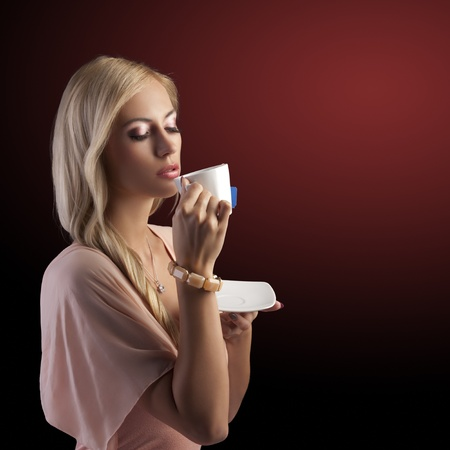 sensual blond girl with hair style drinking a cup of tea in elegant pink dress and bracelet over dark fashion background