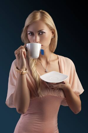 sensual blond girl with hair style in elegant pink dressover holding tea set, drinking tea dark fashion background photo