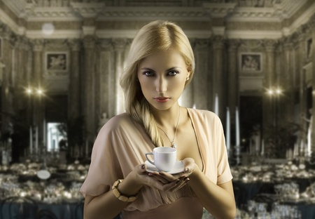 sensual blond girl with hair style holding a cup of coffee in elegant pink dress over dark fashion background