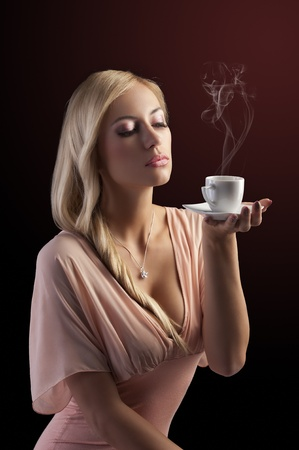 sensual blond girl with hair style holding a  coffee set in elegant pink dress over dark fashion background photo