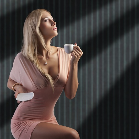 sensual blond woman with hair style holding a cup of coffee in elegant pink dress over dark fashion background photo