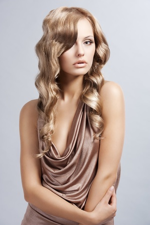vogue: very beautiful and attractive young woman with long blonde hair  in elegant silk dress and with old fashion hair style