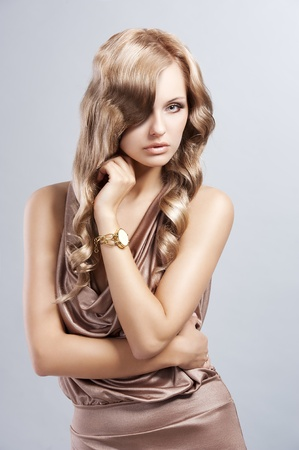very alluring and attractive young blond woman in elegant silk dress and with old fashion hair style