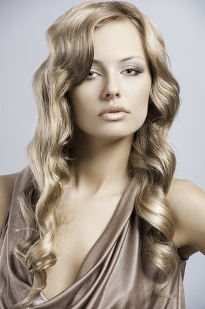 very beautiful and attractive young blond lady in elegant silk dress and with old fashion hair style Standard-Bild