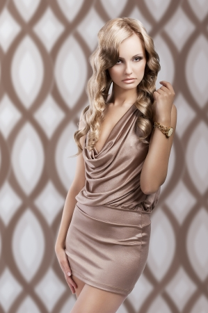 very beautiful and irresistible young blond woman in elegant silk dress and with old fashion hair style