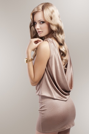 very beautiful and attractive young blond woman in elegant silk dress and with old fashion hair style and golden clock