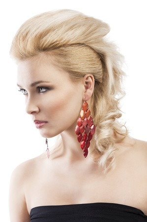 vogue style: sensual portrait of very attractive blond woman with creative hair style and big fashion red earring with black top, she is turned three quarters and looks in front of her