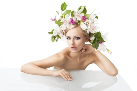 nude fashion model: young sexy beautiful woman with naked shoulder and wearing a big crown of flower and leaves as spring queen, she is behind the table, looks in to the lens with an expression of surpraise. Her right arm is on the table, her right arm is bent and her right