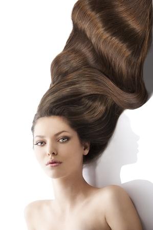 la belleza close-up retrato de la cara de mujer hermosa con largos pelos ondulados oscuros que se establecen en el blanco, que se ve en la lente y su rostro está ligeramente girado a la derecha del anuncio