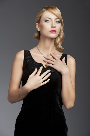 young elegant blond woman wearing black dress with an old fashion hairtyle and necklace jewellery, she looks in to the lens and has both hands over her chest photo