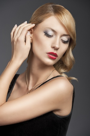 parole: young elegant blond woman wearing black dress with an old fashion hairtyle and necklace jewellery, she looks down at the left and touches her hair with right hand