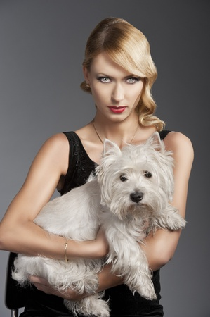 young elegant blond woman wearing black dress with an old fashion hairtyle and necklace jewellery, she looks down at the left and touches her hair with right hand, she is in front of the camera, looks in to the lens and has a dog in her arms. photo