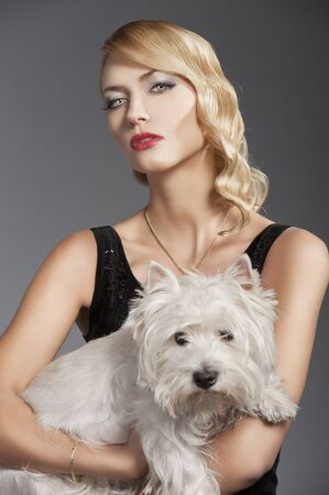 young elegant blond woman wearing black dress with an old fashion hairtyle and necklace jewellery, she looks in to the lens with actractive eyes and takes the dog in her arms photo