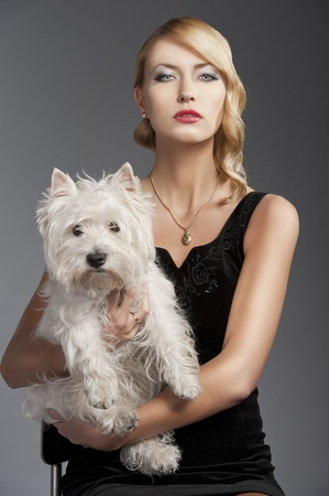 young elegant blond woman wearing black dress with an old fashion hairtyle and necklace jewellery, she is in front of the camera, takes a dog in her arms and looks in to the lens photo