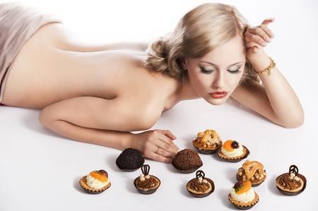 naked woman: сексуальная голая женщина с длинными светлыми волосами, устанавливающий на белый с некоторым теста рядом с ней в акте, чтобы съесть их, она выглядит печенья и имеет правую руку рядом с головой
