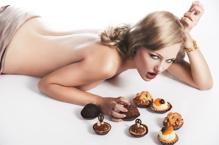 sexy naked woman with long blond hair laying down on white with some pastry near her in act to eat them, she looks in to the lens, takes one pastry with left hand and her mouth is open photo