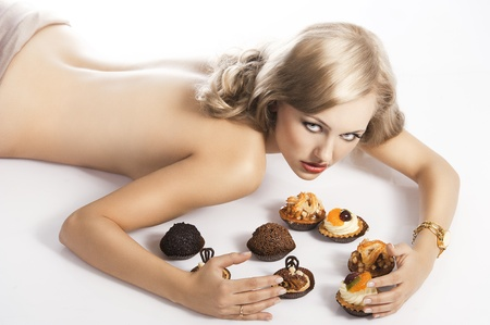 sexy naked woman: sexy naked woman with long blond hair laying down on white with some pastry near her in act to eat them, she looks in to the lens with actractive eyes and her arms are around the pastries Stock Photo