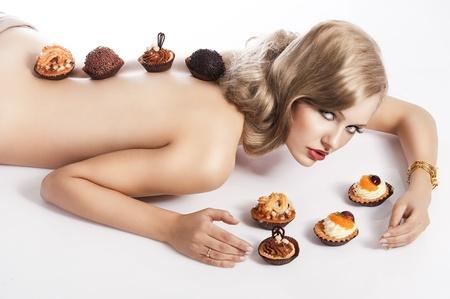 mujer sexy desnuda: sexy mujer desnuda con el pelo largo y rubio que se establecen en blanco con un poco de pasteles cerca de ella en el acto de comer, ella se ve en la lente y tiene unos pasteles en la espalda Foto de archivo