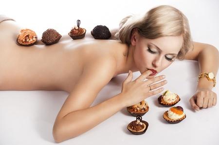 mujer sexy desnuda: sexy mujer desnuda con el pelo largo y rubio que se establecen en blanco con un poco de pasta junto a ella en el acto de comer, ella tiene algunos pasteles en su espalda. Foto de archivo