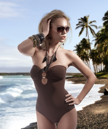 glamour nude: glamour shot of a sexy blonde posing in a brown swimsuit and wearing fashion sunglasses Stock Photo