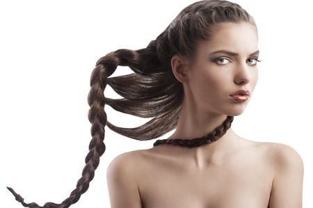 portrait of a pretty long haired brunette with a moving braid hair style on white