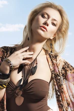 beauty breast: blond sexy beautiful young woman wearing a flower scarf over her body with brown swimsuit with jewellery. She is slightly slanted to the left, looks in to the camera with sexy expression and she touches her nech with right hand.