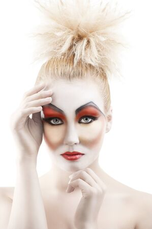 faceart: Portrait of young woman with colorful creative make-up like a doll and very cute hair style. she is in front of the camera, looks in to the lens and has both hands near the face Stock Photo