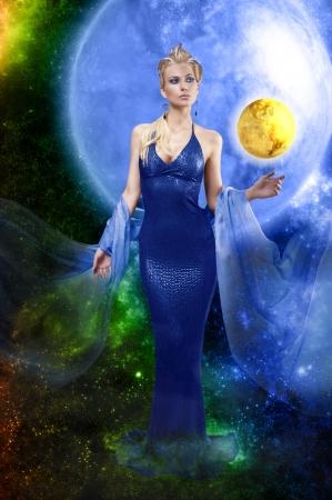 robo: atractiva mujer impresionante con un largo vestido azul de cuero elegante y una estola jugando con el planeta de oro en el fondo del espacio Foto de archivo