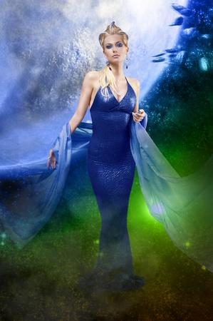 maquillaje de fantasia: atractiva mujer impresionante con un vestido largo de cuero elegante y una estola con la creativa maquillaje y peinado en el fondo del espacio estelar