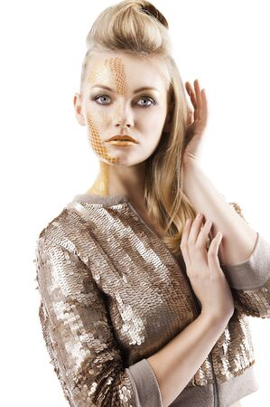 glitter makeup: Blond beautiful creature with sequin jacket and creative make up making and hair stylish, she looks in to the lens and her left hand is near the face and  touches the right arm.