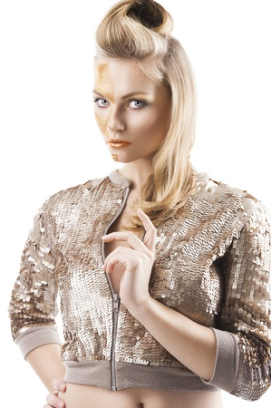 Blond beautiful creature with sequin jacket and creative make up making and hair stylish, she is turned of three quarters, looks in to the lens and her left hand is near the chest Stock Photo - 12156854