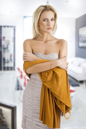 elegant pretty young woman with a long scarf and a lighter dress, she looks in to the lens and her arms are crossed photo