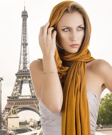shawl: elegante mooie jonge vrouw met een lange sjaal en een lichtere jurk. Ze kijkt naar links met de sjaal op het hoofd en ze raakt het haar met rechterhand