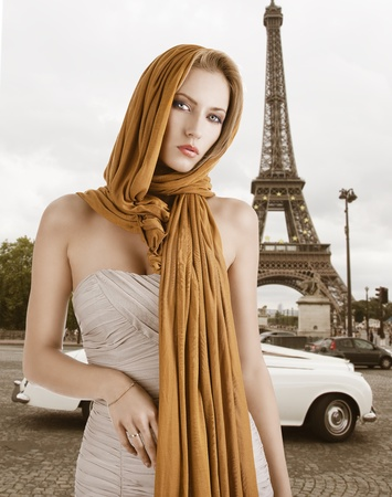 elegant pretty young woman with a long scarf and a lighter dress. She looks in to the lens and has the scarf on the head, the right hand is on her belly. photo
