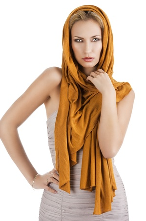 scarf: elegant pretty young woman with a long scarf and a lighter dress. She is in front the camera, looks in to the lens. The right hand is on the hip and the left hand is near the neck