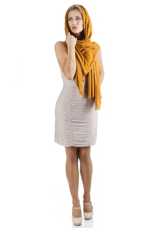 elegant pretty young woman with a long scarf and a lighter dress. She is in front of the camera, looks at right and she has the left hand near the neck. photo