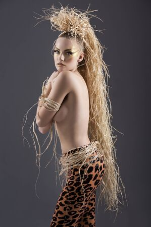 beautiful and sexy girl with raffia hair and a ethnic jungle costume in a shot over dark with creative make up photo
