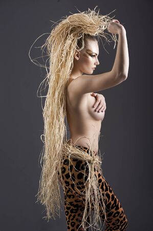 alluring and sexy girl with raffia hair and a ethnic costume in a shot over dark with creative make up photo