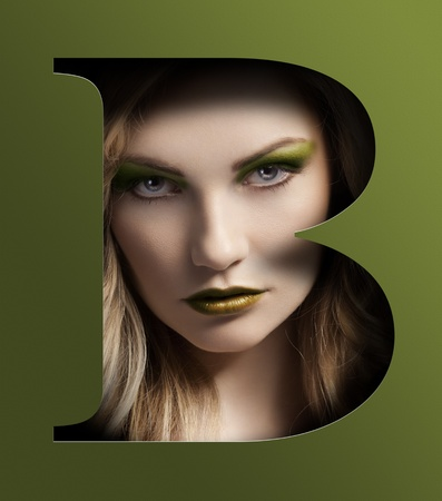 letter b: close up beauty portrait of young pretty woman behind a color green letter B