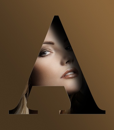 close up beauty portrait of young pretty woman behind a color brown letter A photo