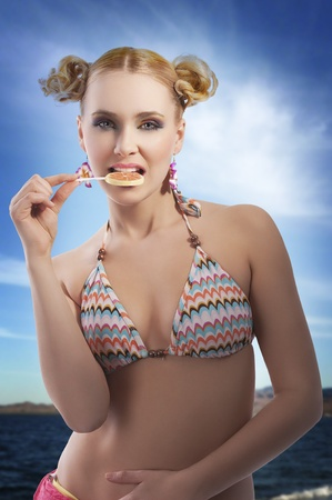 beautiful young woman with blond hair and stylish in bikini swimsuit eating candy photo
