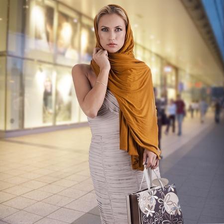 mooie elegante dame met oranje sjaal en het winkelen zak over wit