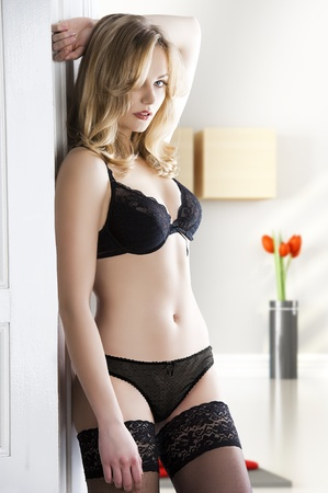 very sexy and attractive blond girl indoor wearing a bikini lingerie and stocking , taking pose near door, she is turned of three quarters, looks in to the lens and has the left arm behind the head.