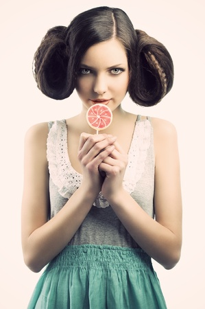 young beautiful brunette with a creative luxury hair style and a colored lollipop. She is in front of the camera, looks in to the lens with an a sly expression and takes the lollipo near the mouth photo