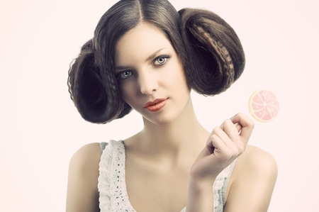 young beautiful brunette with a creative luxury hair style and a colored lollipop. She looks in to the lens and has the face slightly folded at right. She tales the lollipop with left hand. photo