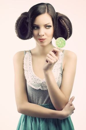 young beautiful brunette with a creative luxury hair style and a colored lollipop, she looks the lollipop and takes that with the left hand.  photo