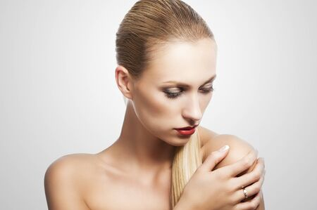 blond pretty woman in a beauty portrait with wet hair and a straight tail over shoulder. She looks down at left, the tail is over the left shoulder and she has a right hand on that. Stock Photo - 12376954